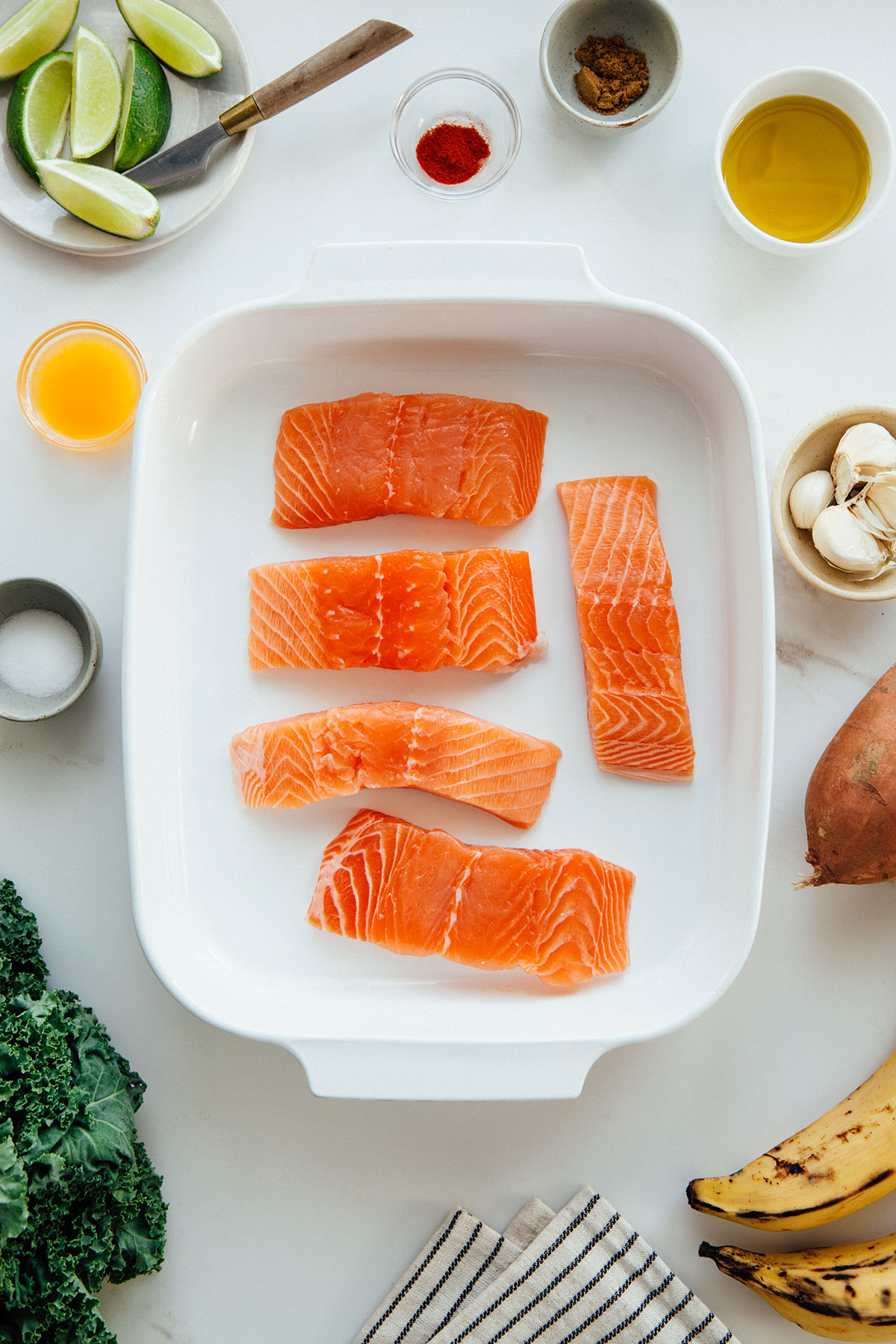 A dish of fresh salmon filets surrounded by ingredients.