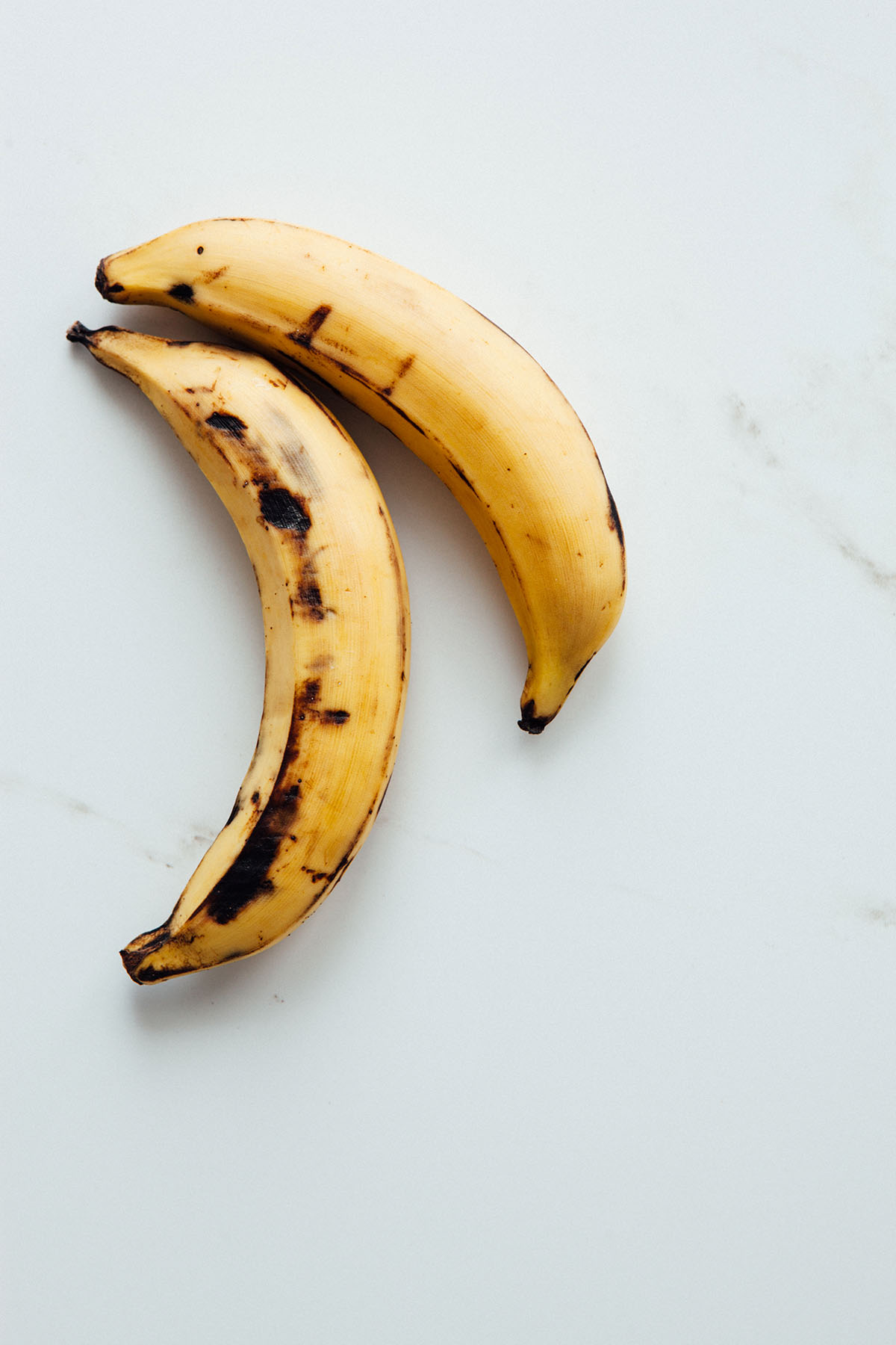 Two plaintains laying on a marble surface.