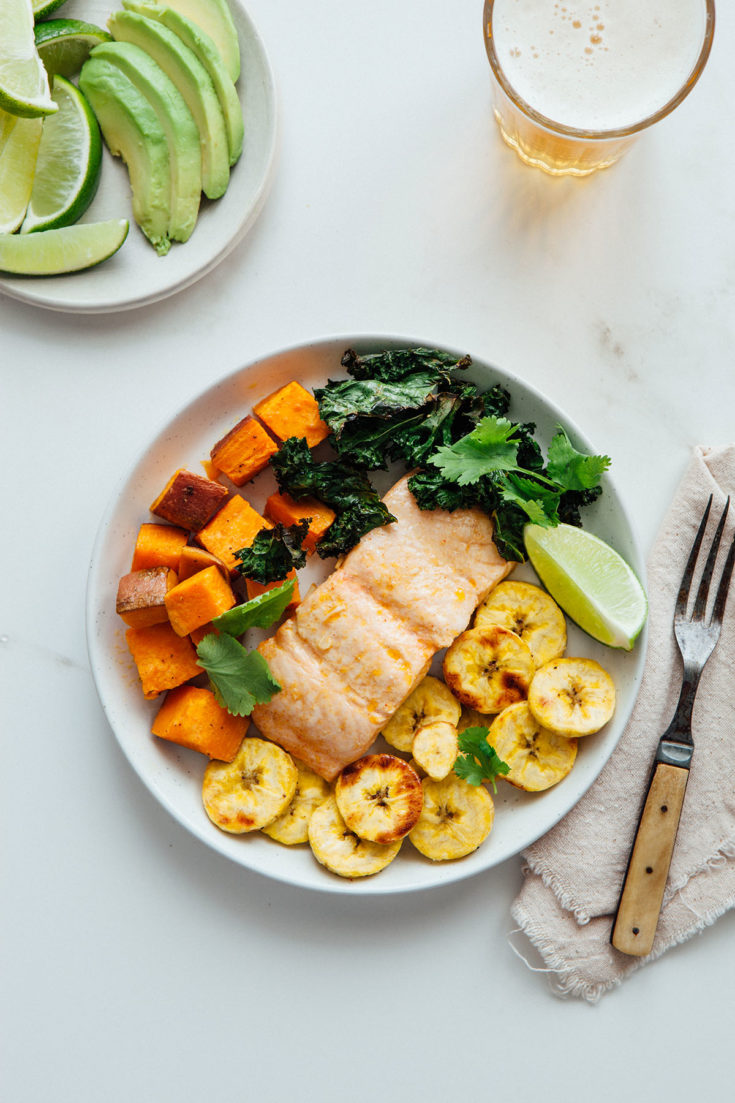 A plate of Cuban-inspired sheet pan salmon with plantains, roasted sweet potatoes, kale chips, and a beer.