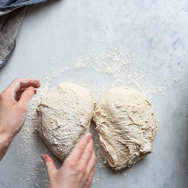 overhead image of bakerforming sourdough dinner rolls.