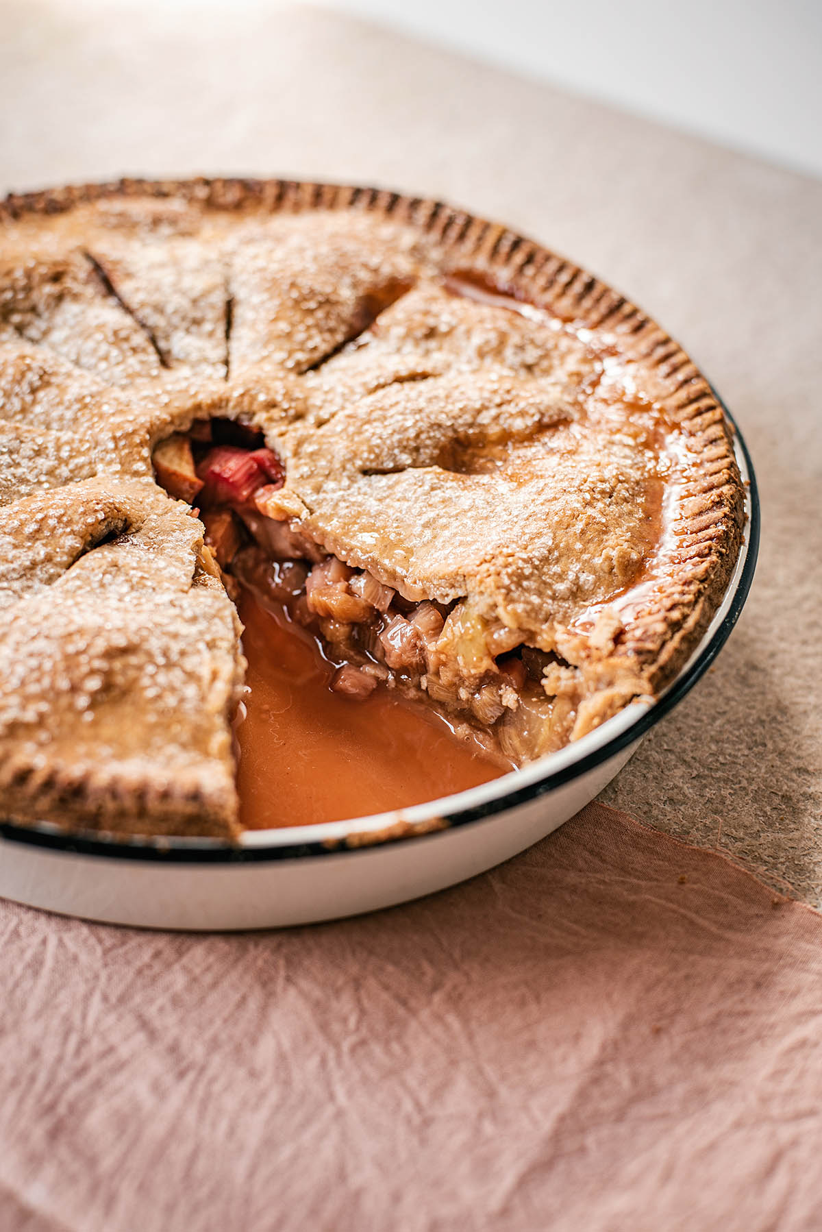 A fully baked aplpe rhubarb pie with one slice removed.
