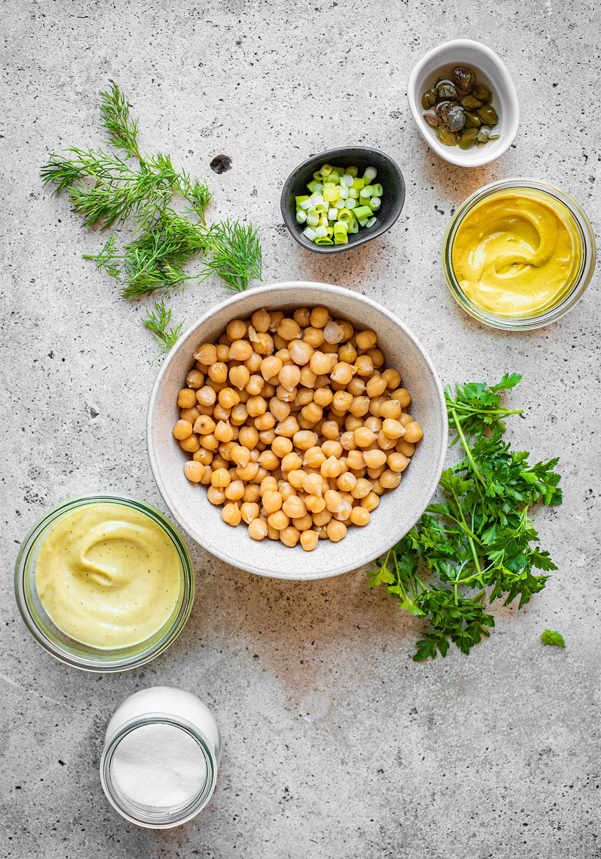 A bowl of chickpeas surrounded by mustard and herbs.