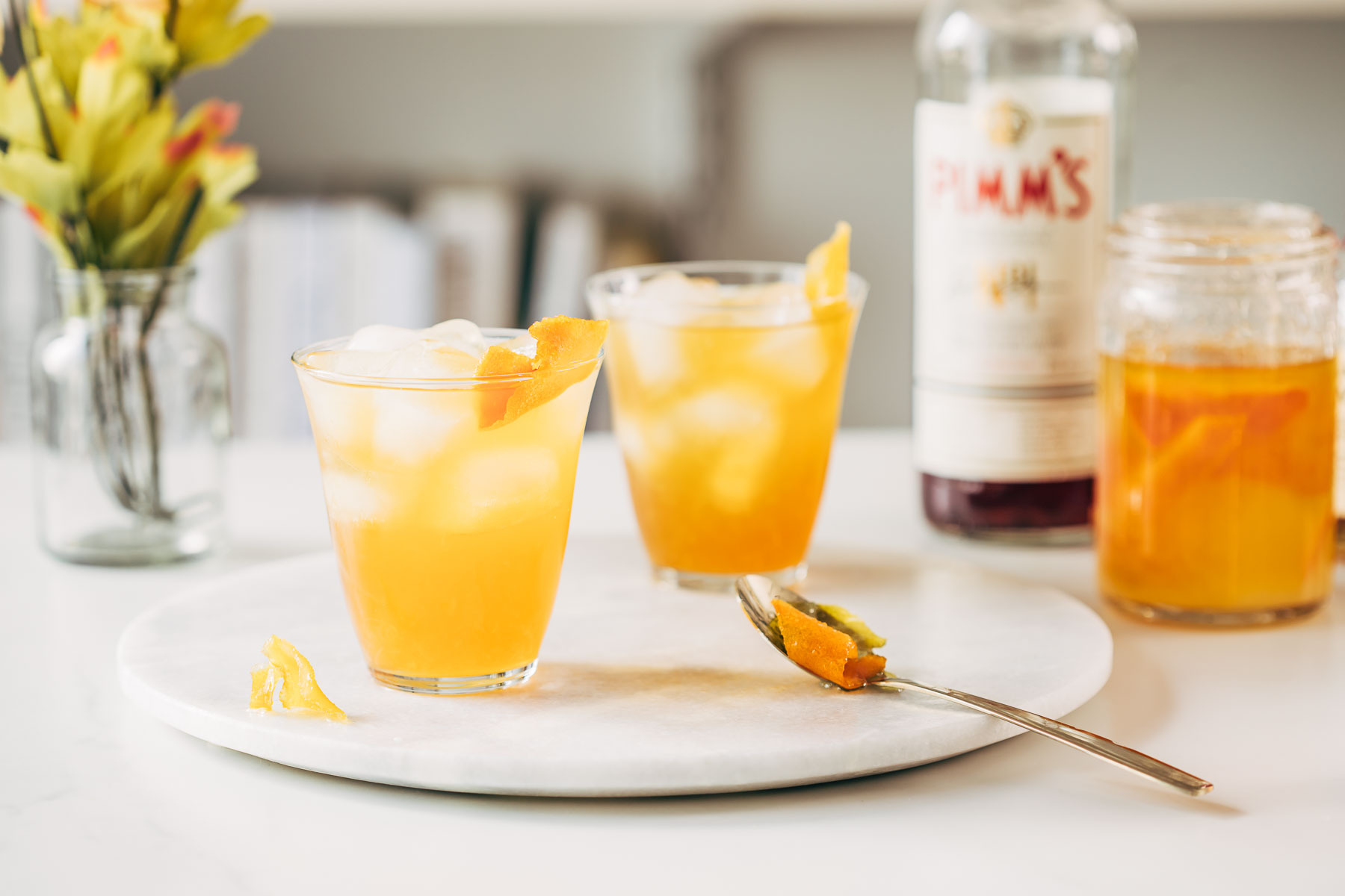 Two yellow cocktails on a marble board with a bottle of Pimm's in the background.