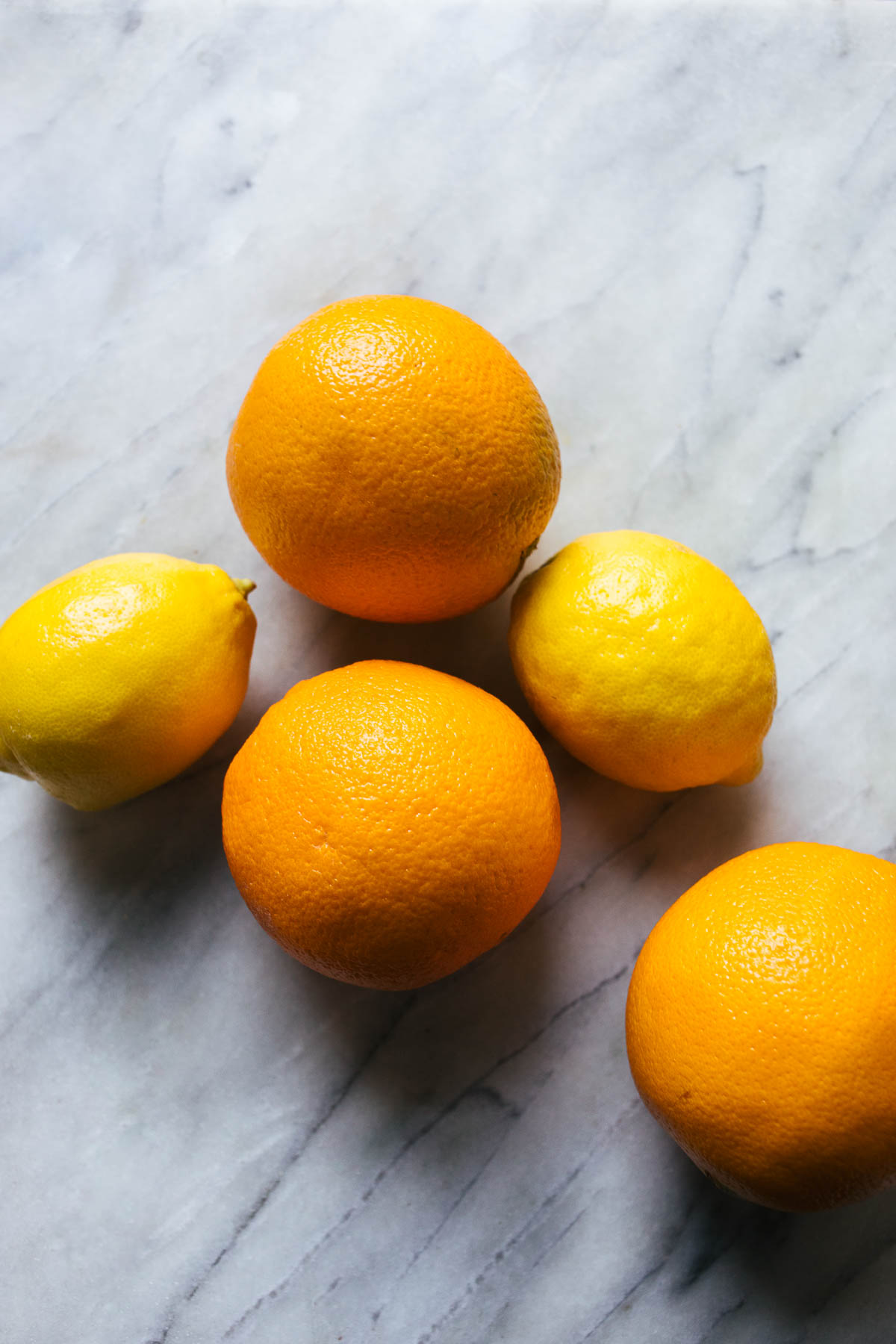 Oranges and lemons on a marble background.