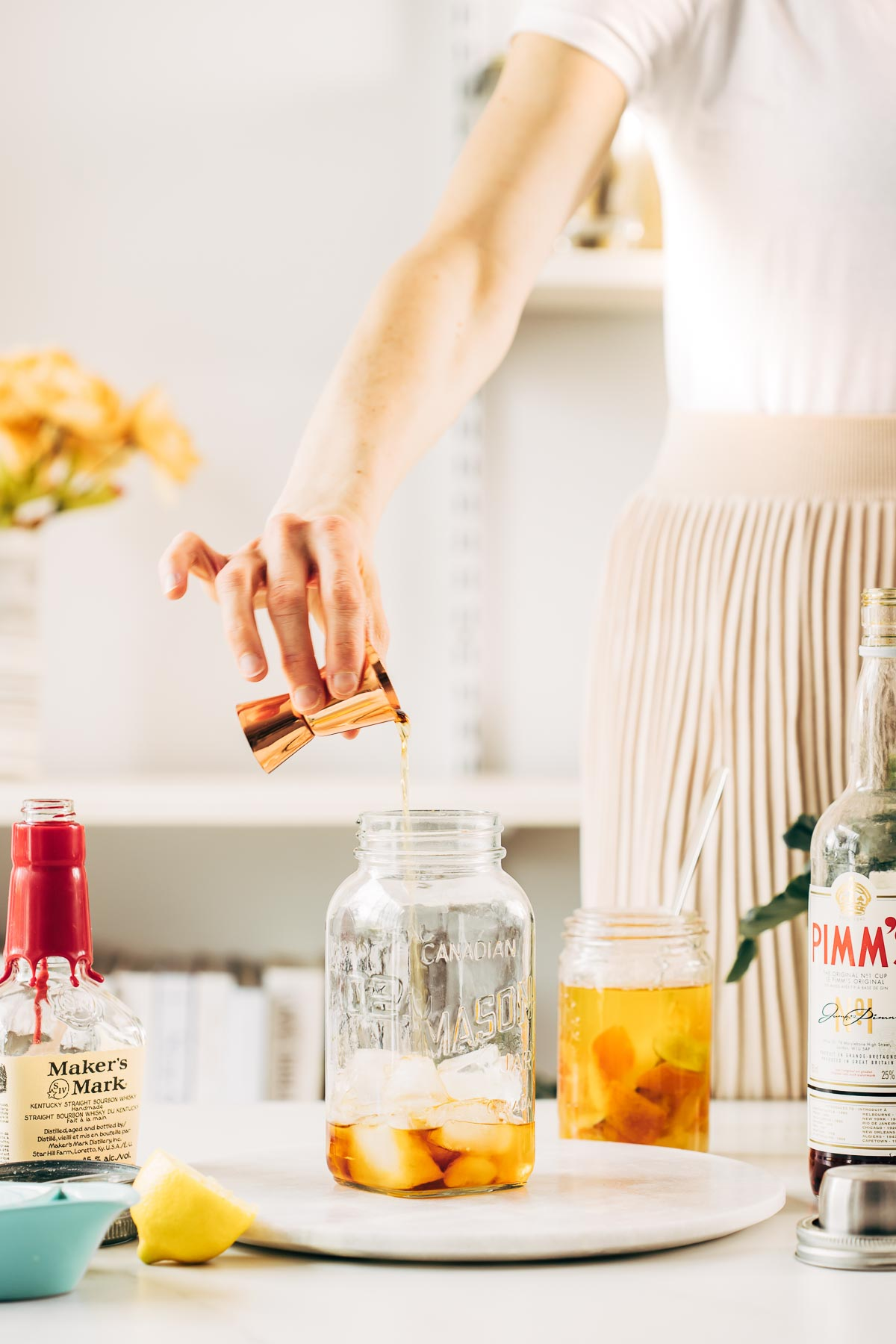 A woman's hand pouring liquid into a jar.