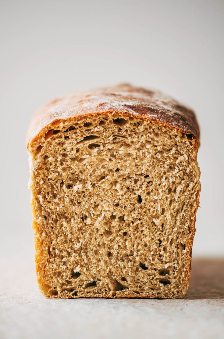 Close up cross section of a sliced loaf of sourdough sandwich bread.
