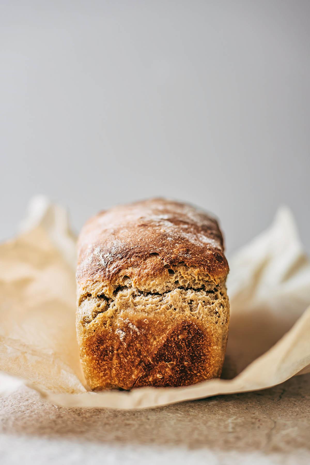 A loaf of sourdough sandwich bread on a piece of parchment paper.