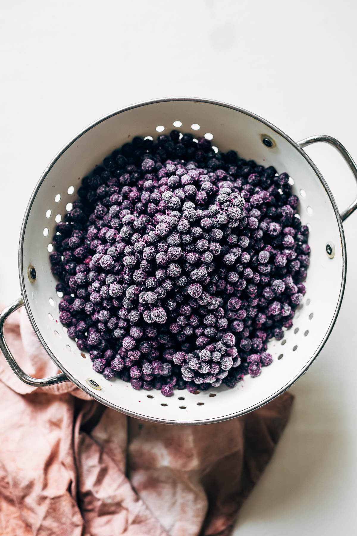 Frozen blueberries in a white colander.