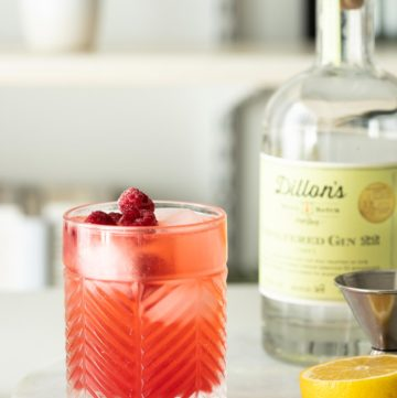 Pink gin basil smash with ice and fresh raspberries.