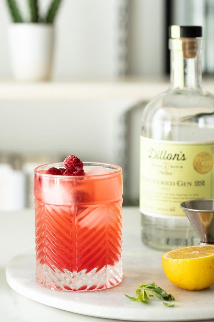 Pink gin basil smash with ice and fresh raspberries.