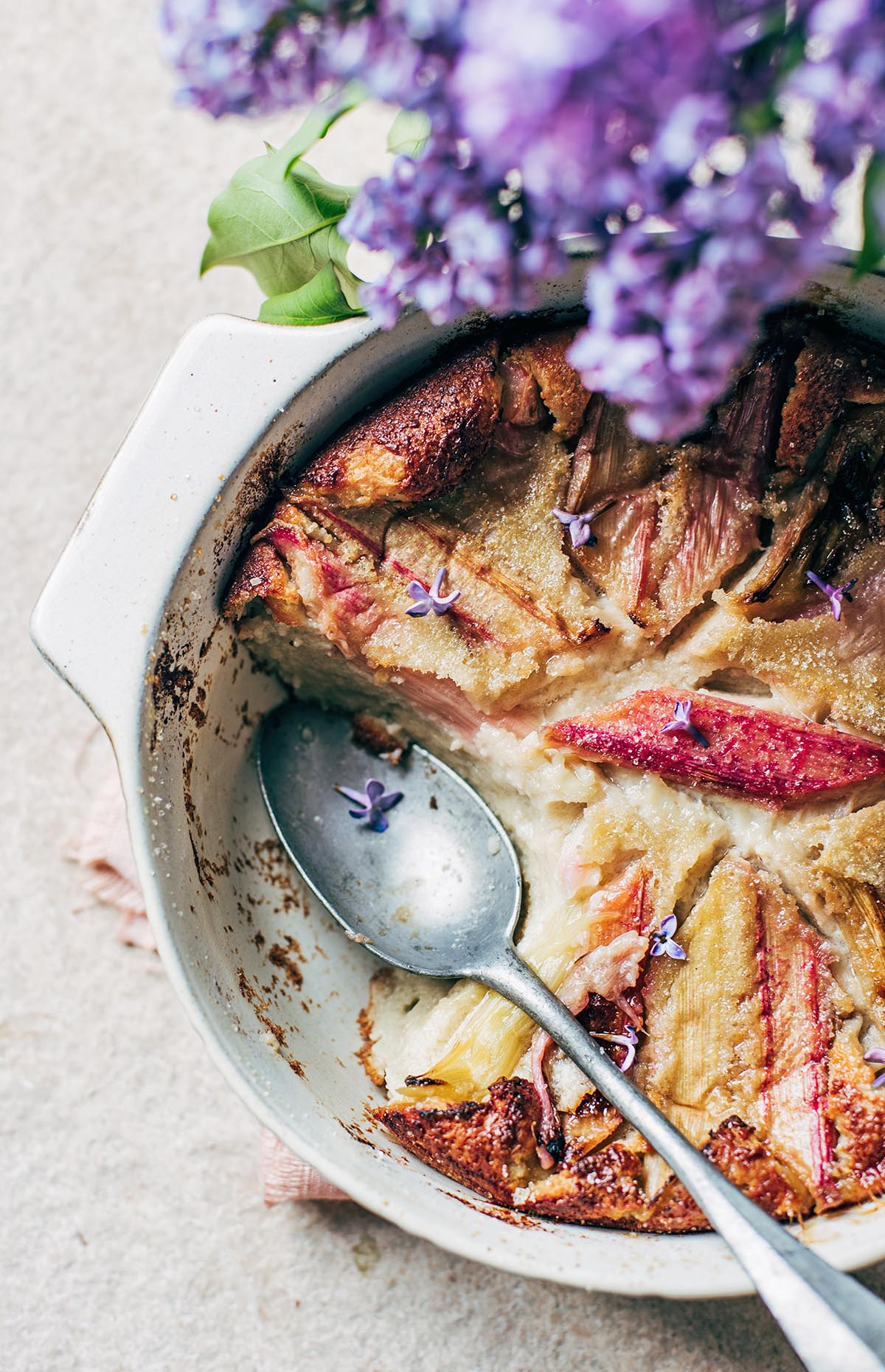 Rhubarb clafoutis with a large antique spoon.