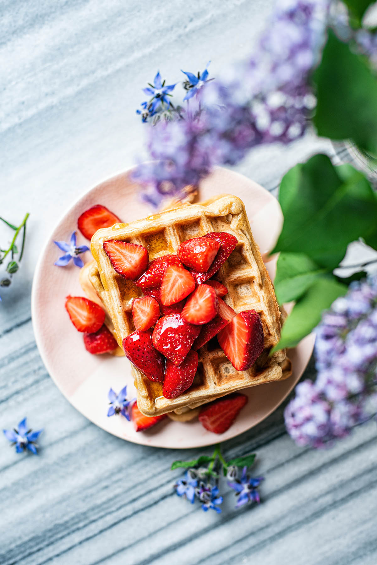Waffles, from above, topped with strawberries and lilacs in foreground.