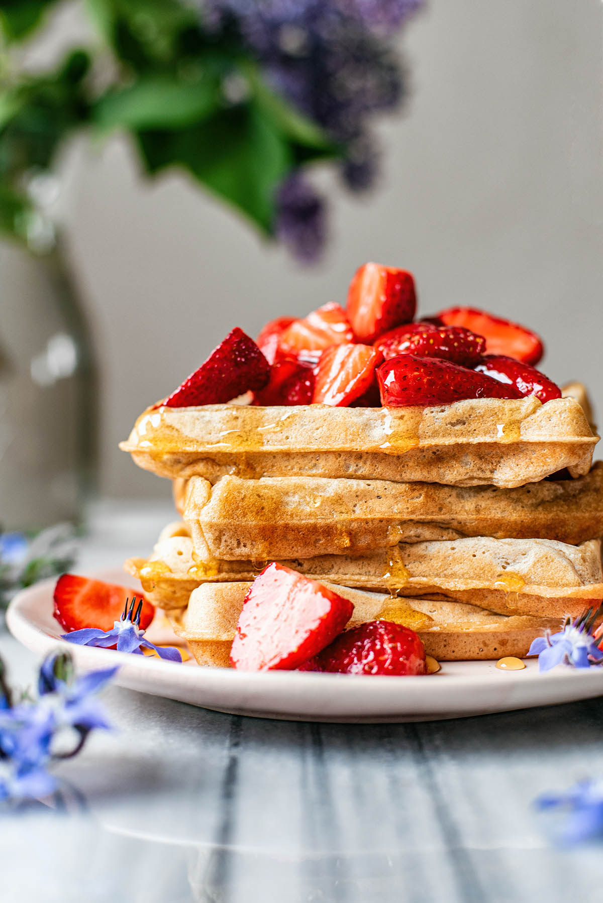 Stack of sourdough waffles topped with strawberries and maple syrup.