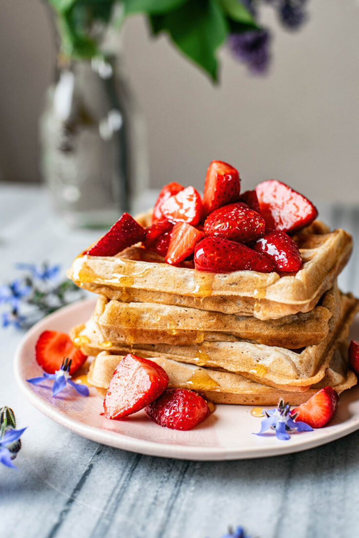 Stack of square waffles topped with strawberries.