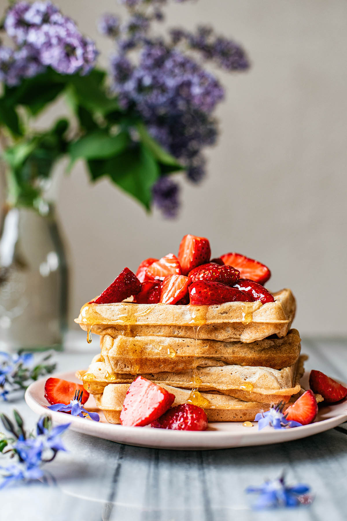 Stack of sourdough waffles topped with strawberries.