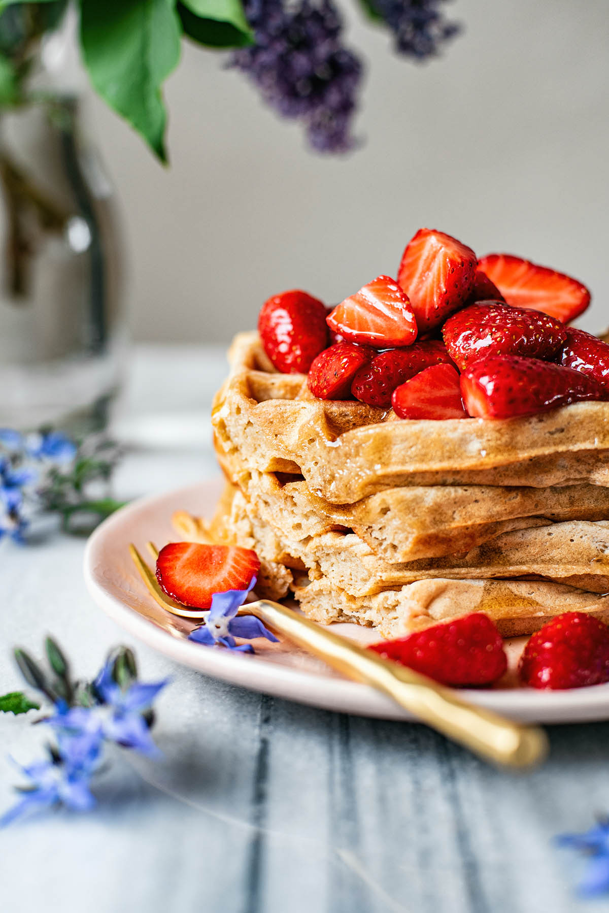 Stack of square waffles topped with strawberries, cut to show interior texture.