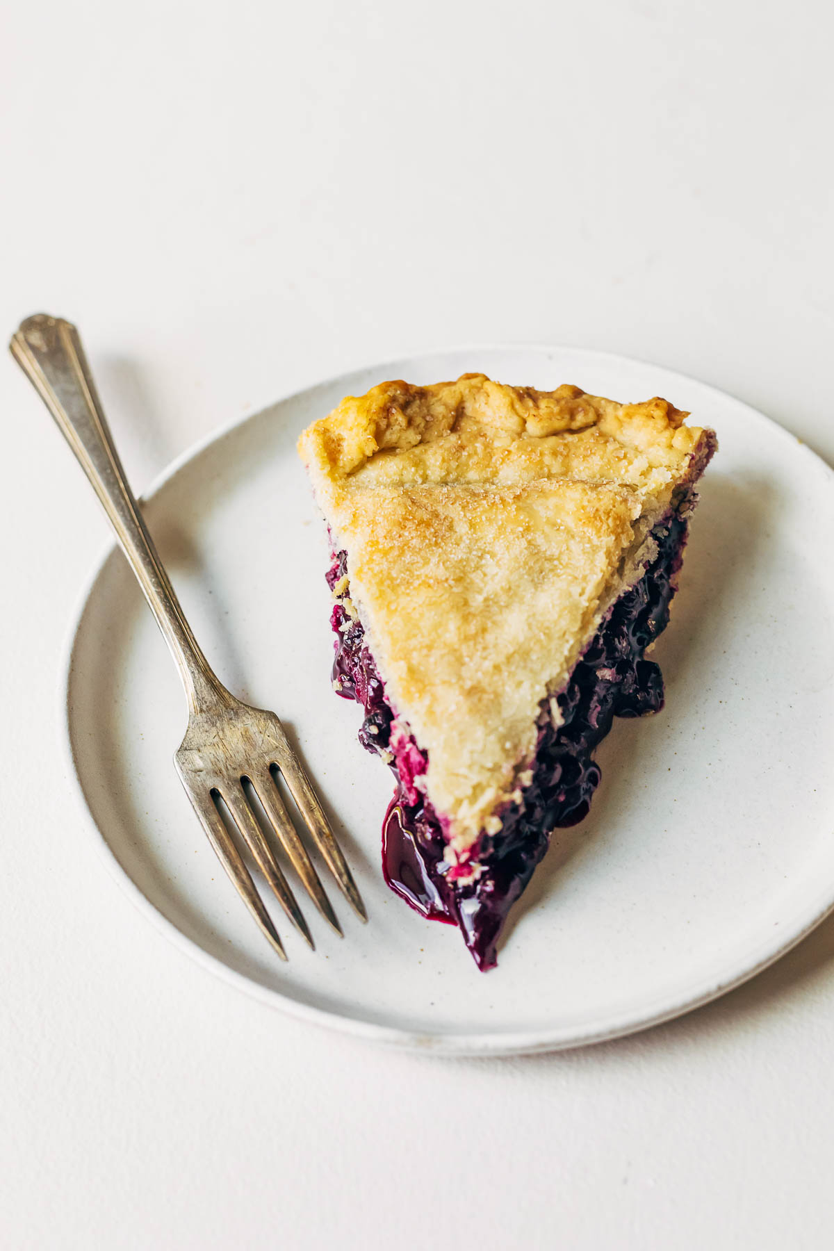 Slice of blueberry pie on a plate with a fork.