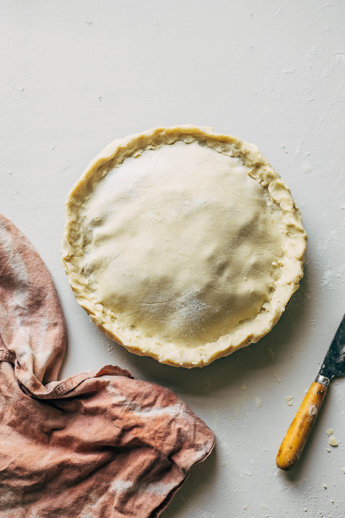 An unbaked pie dough before the edges have been crimped on a white surface with a knife and a pink linen nearby.