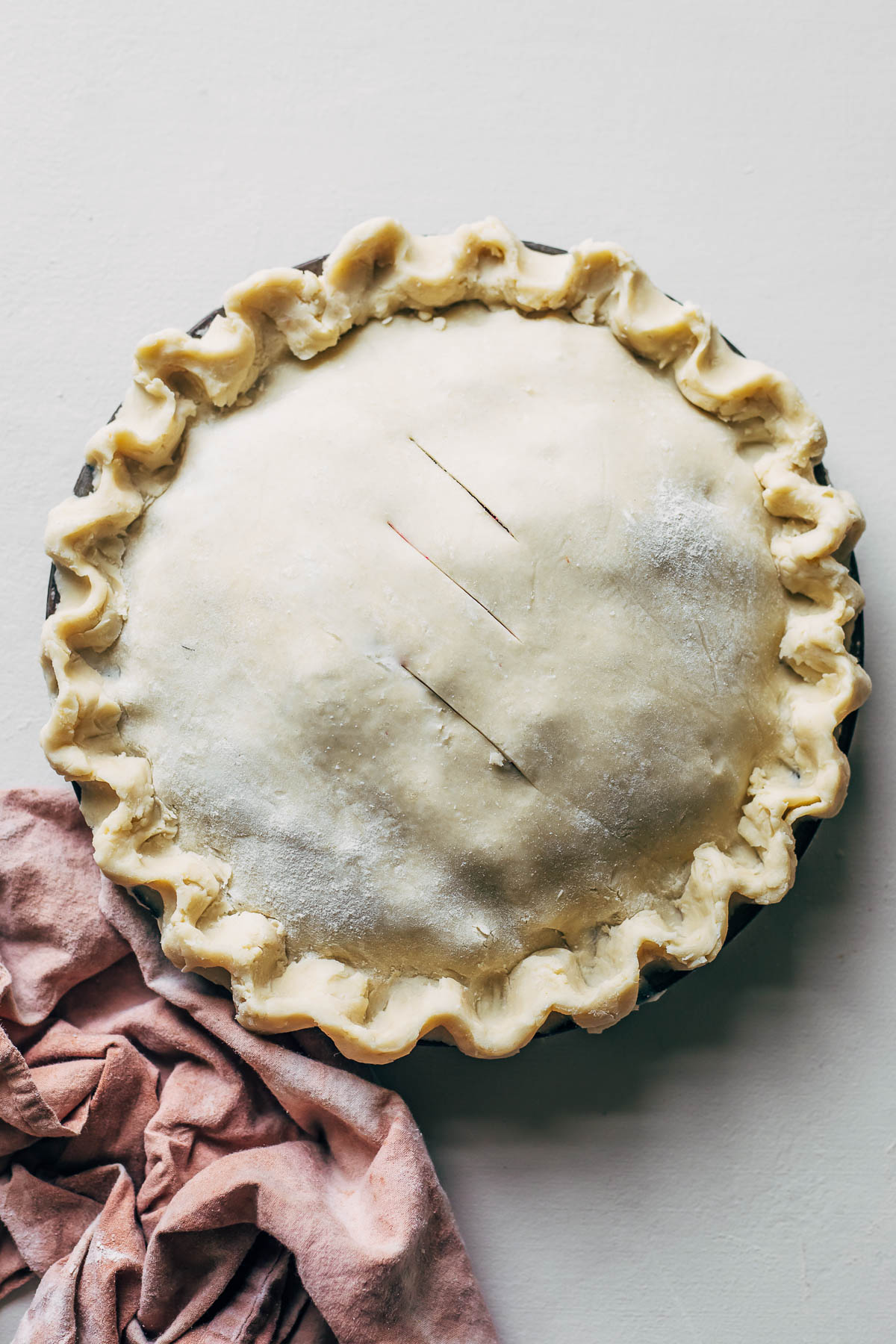 An unbaked pie with vegan pie dough and a crumpled pink linen on a white surface.
