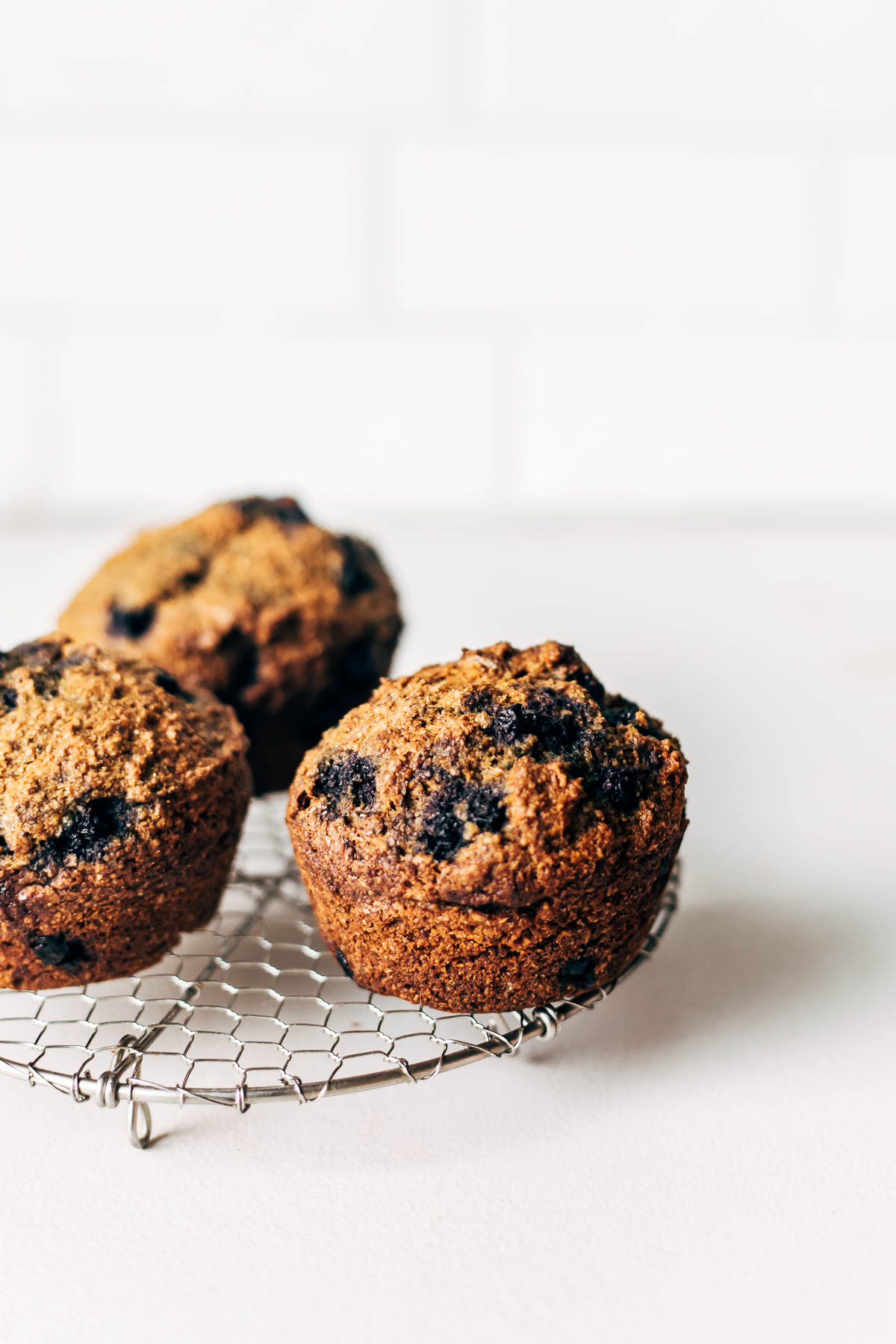 Three bran muffins on a small wire rack.