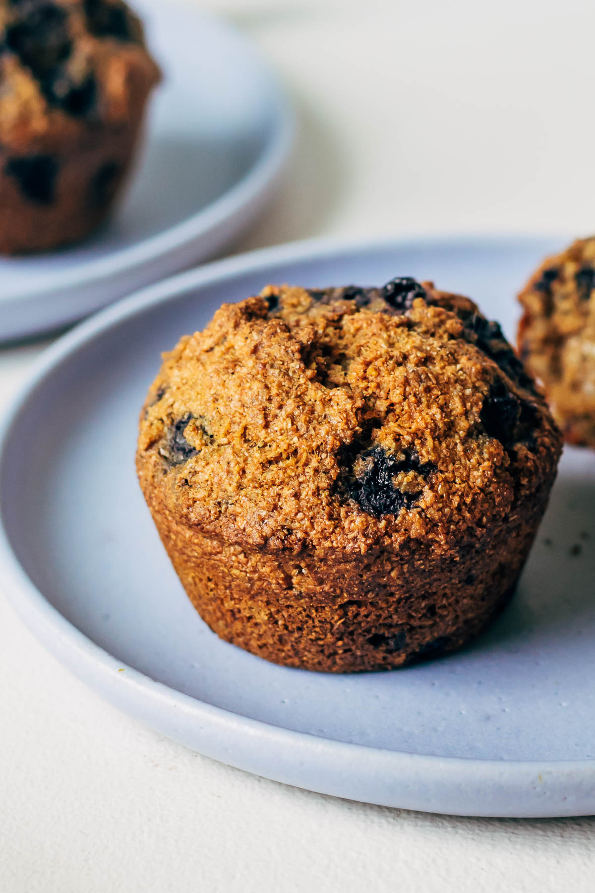 Close up of blueberry bran muffin on a plate.