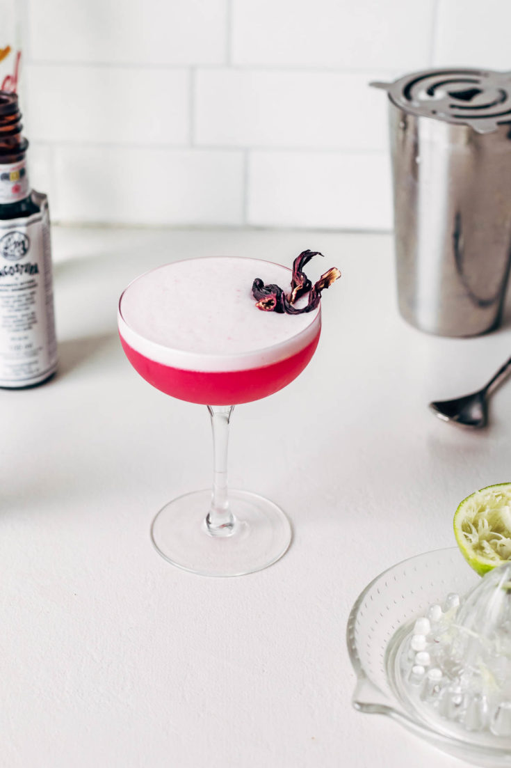 A hibiscus sour cocktail on a white countertop.