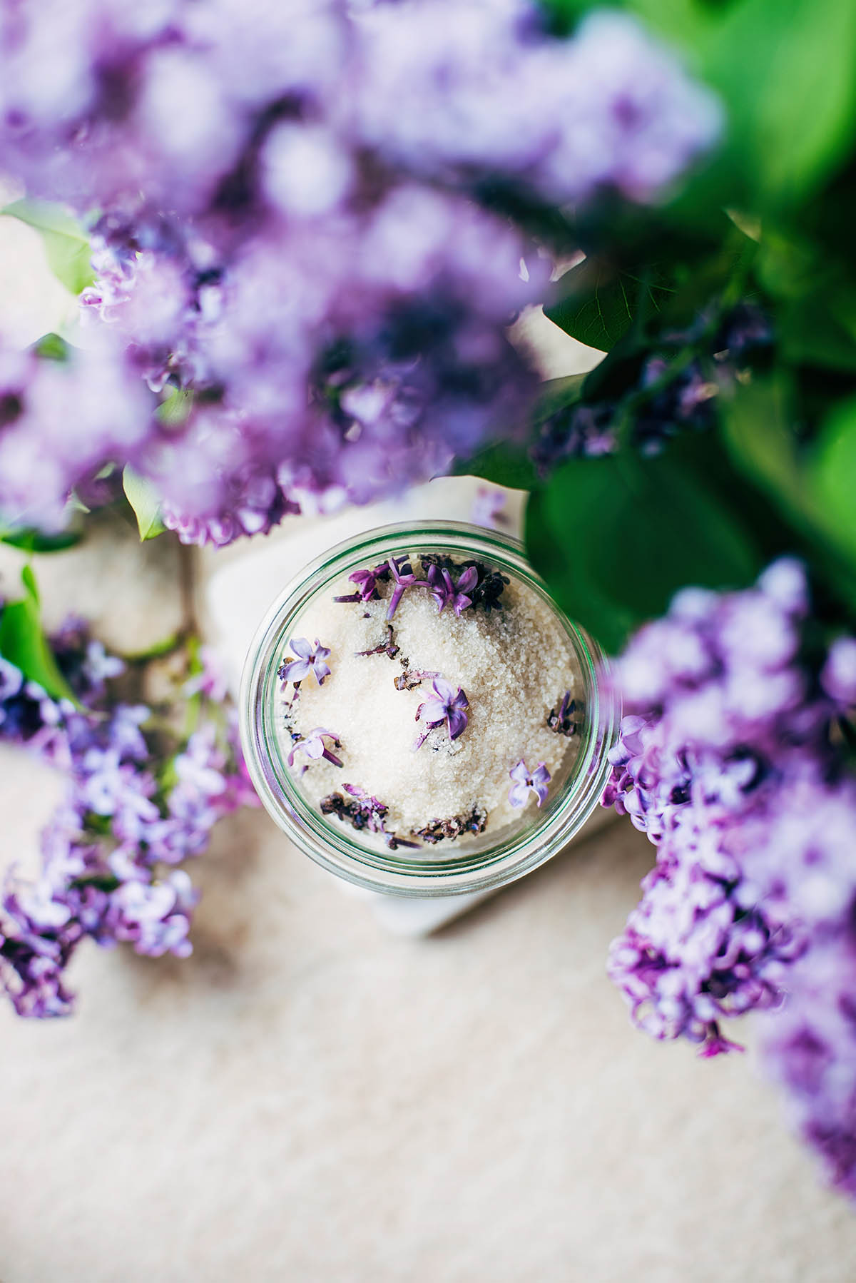 Lilac sugar in a glass jar framed by lilac blossoms.
