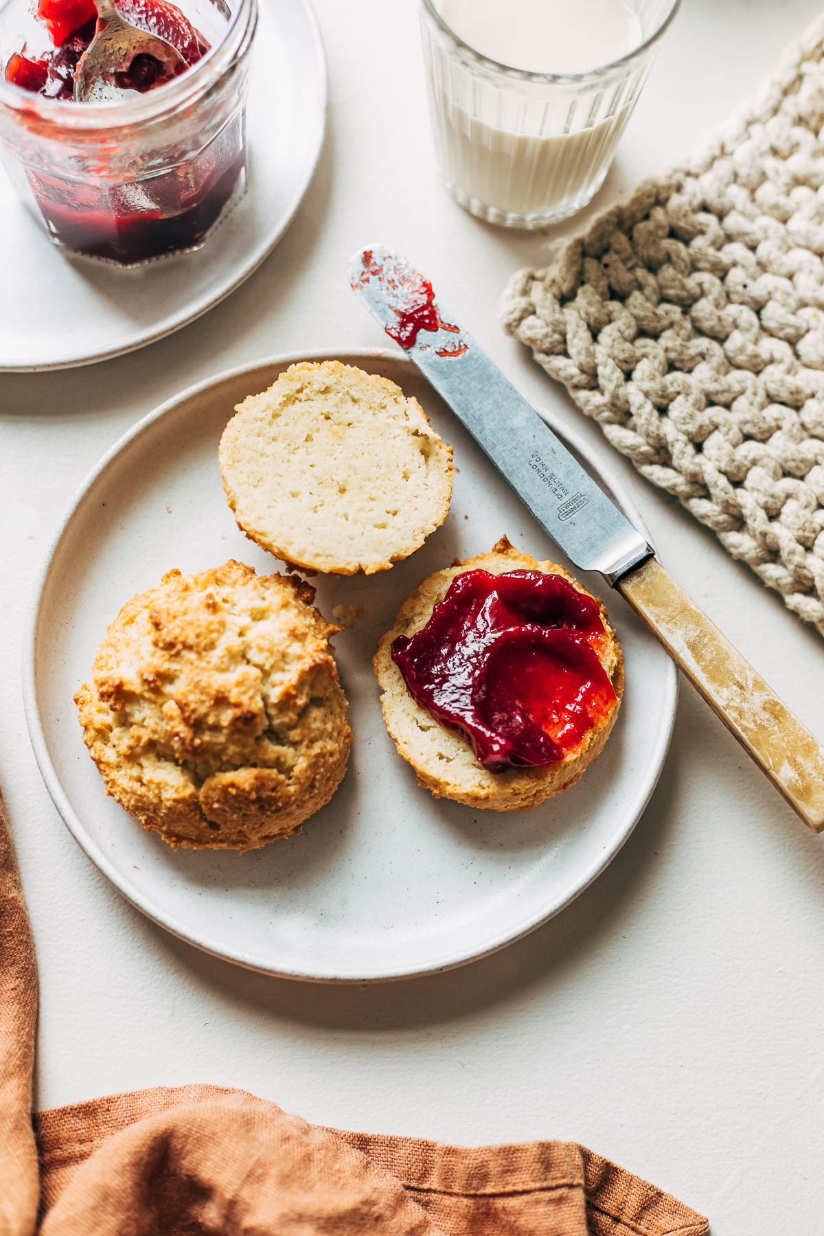 Two almond flour biscuits on a plate, one sliced and topped with jam.