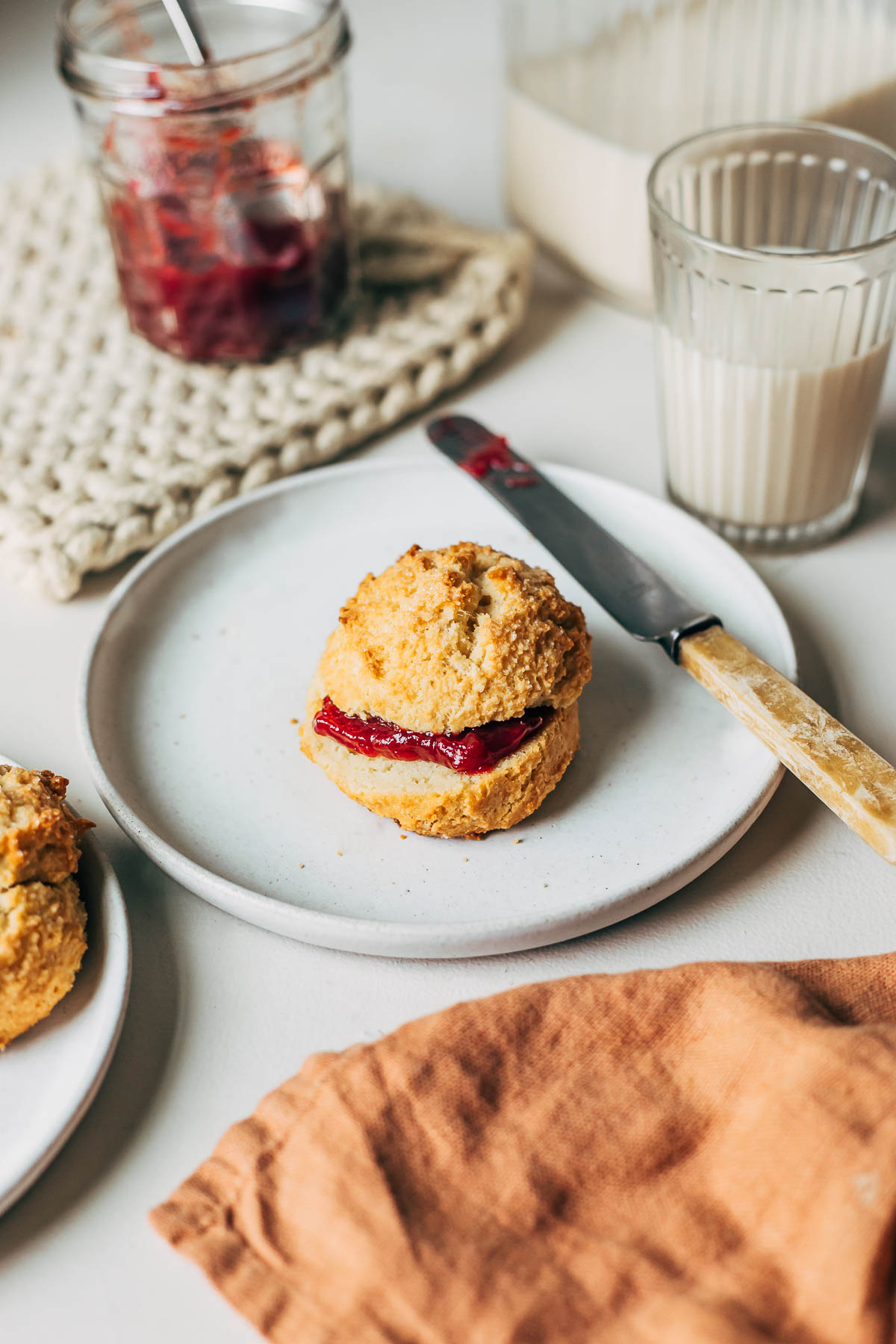 Biscuit on a plate sandwiched with red jam.