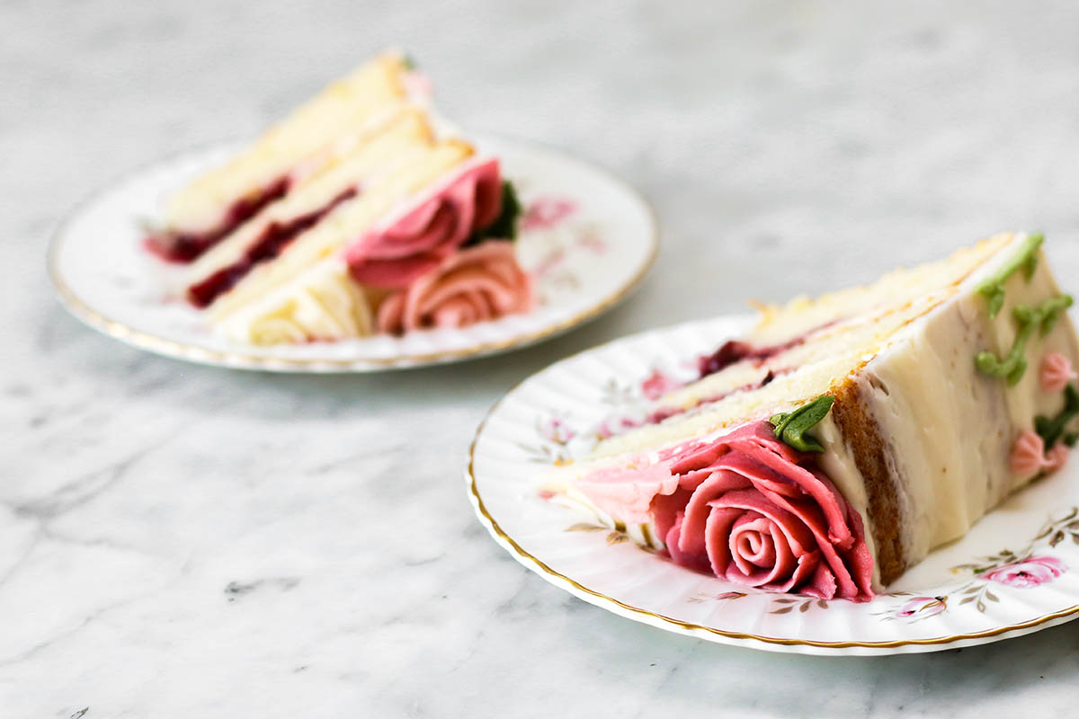 Two slices of lemon buttermilk cake with raspberry filling on small plates.