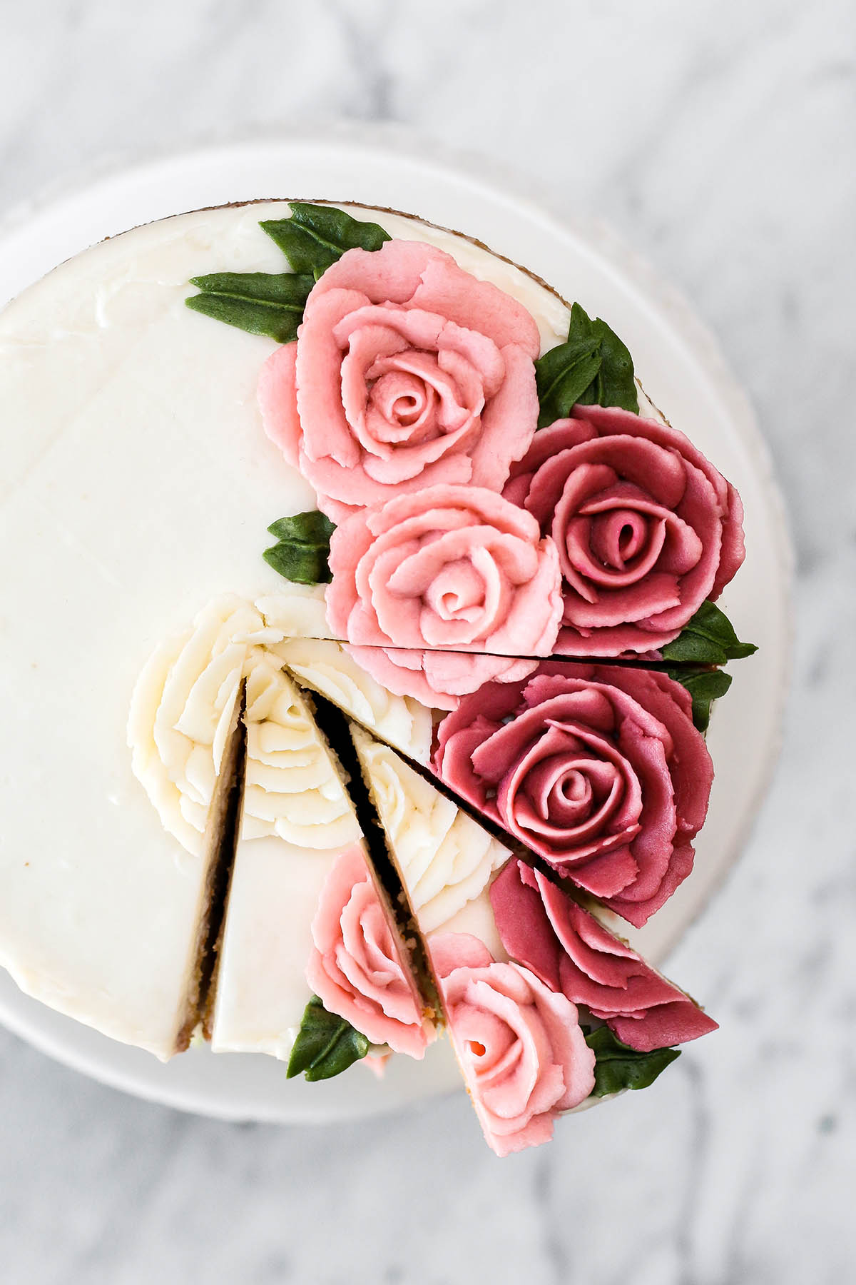 A lemon buttermilk cake with buttercream roses on the top and three slices cut, top down view.