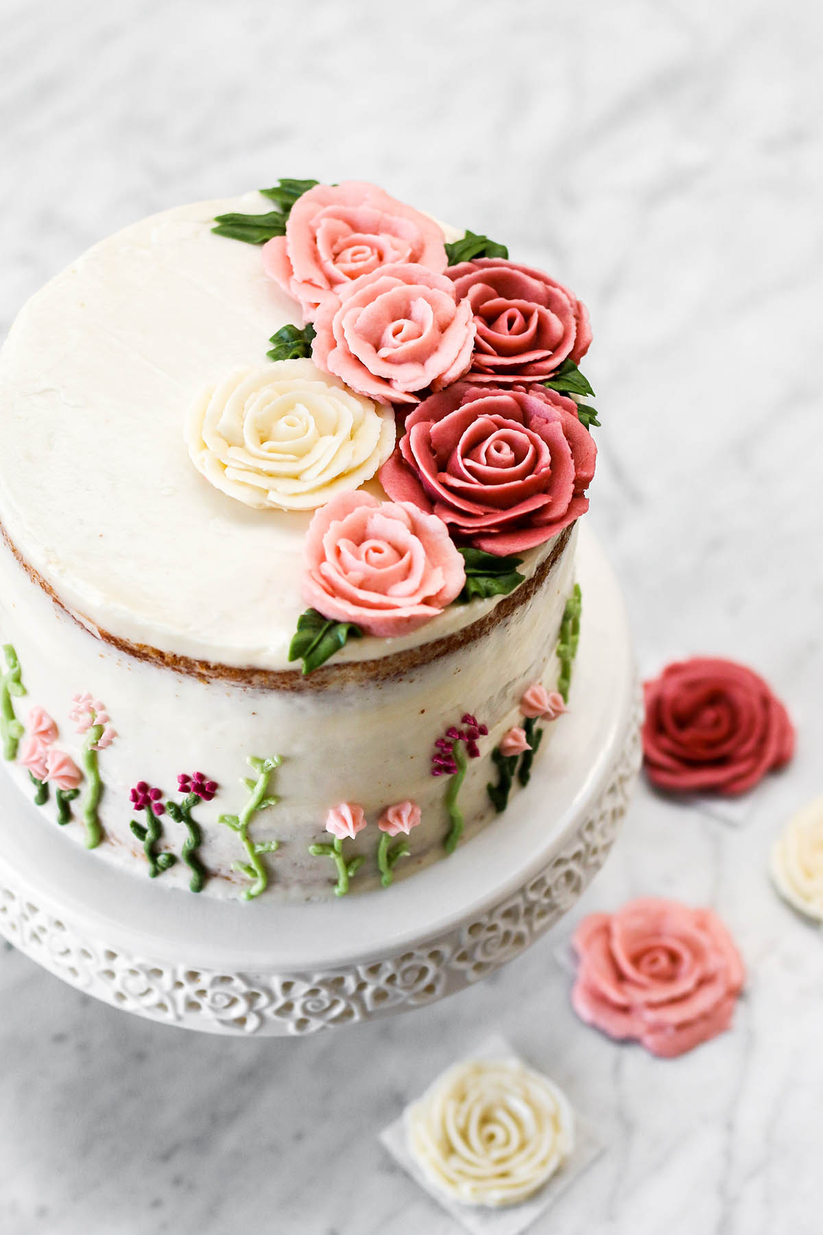 A tall cake on a cake stand with buttercream roses on top and small flowers on the sides.