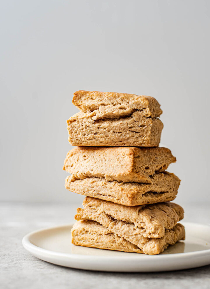 Three square biscuits stacked on a plate.