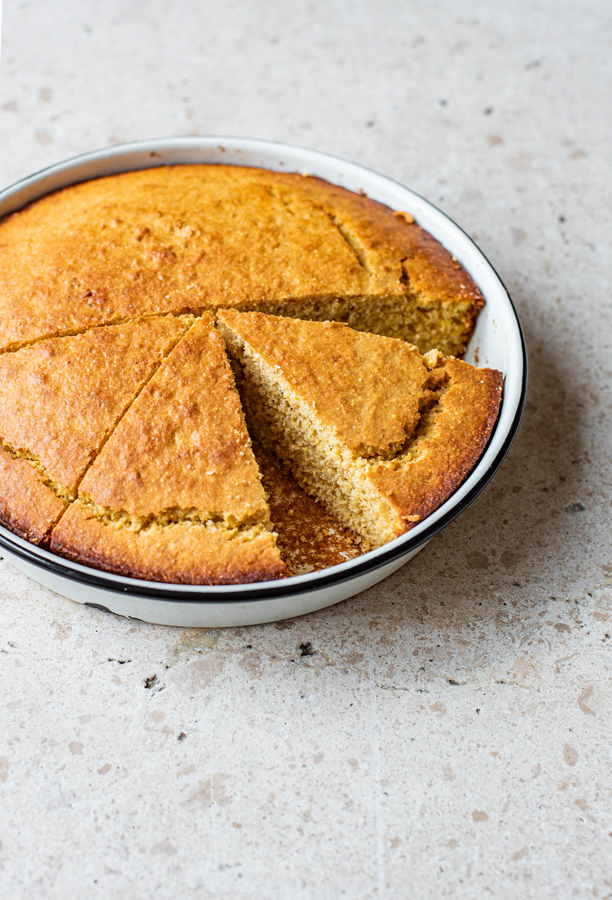 Cornbread in a round tin, half cut into triangles.