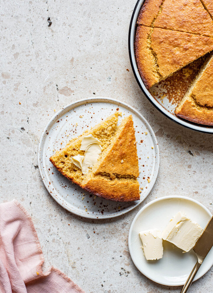 A triangle of cornbread on a plate, cut in half with butter in the middle and more cornbread in the corner.
