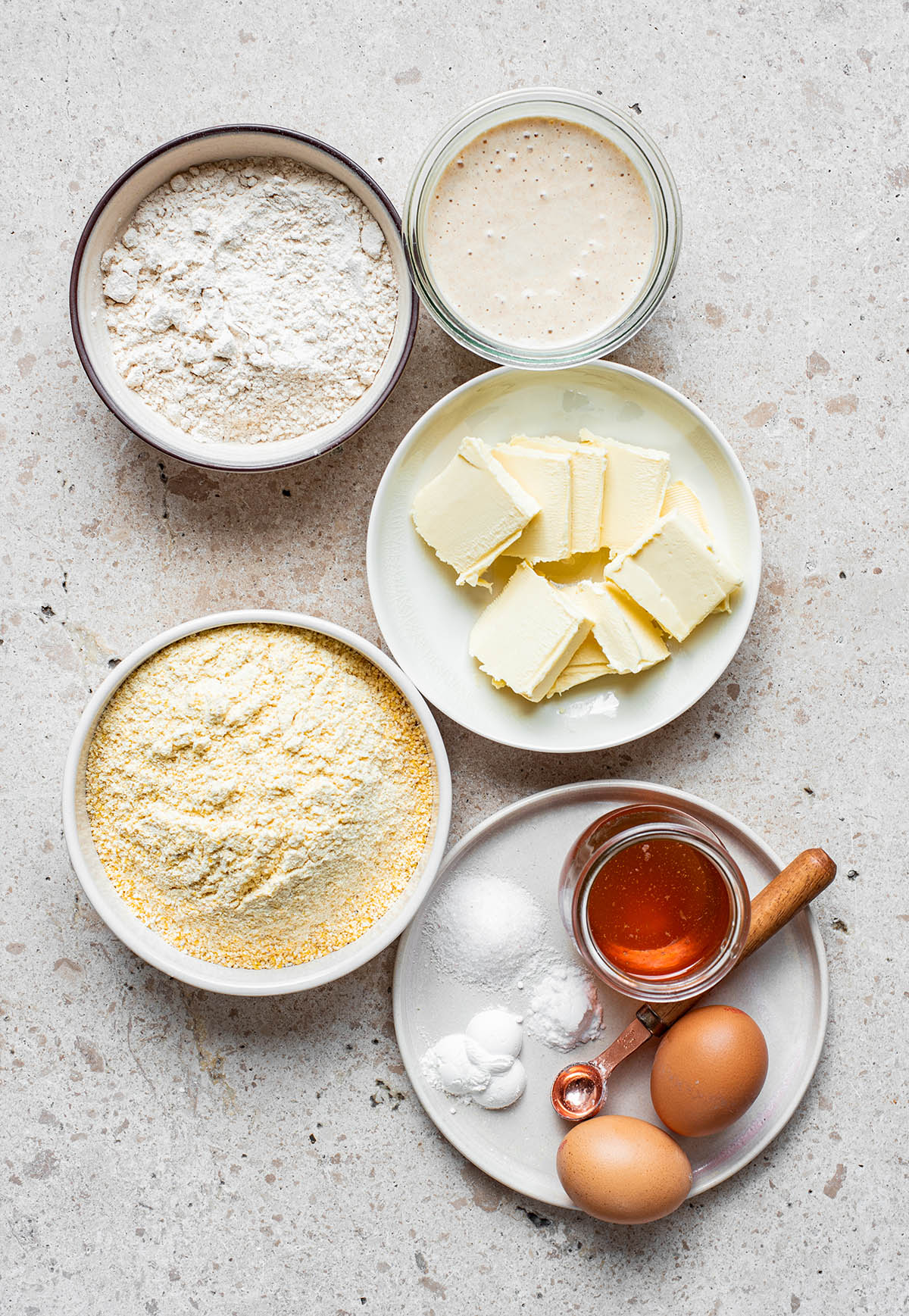 Sourdough cornbread ingredients: discard, flour, cornmeal, butter, honey, salt, baking soda, baking powder, and eggs.