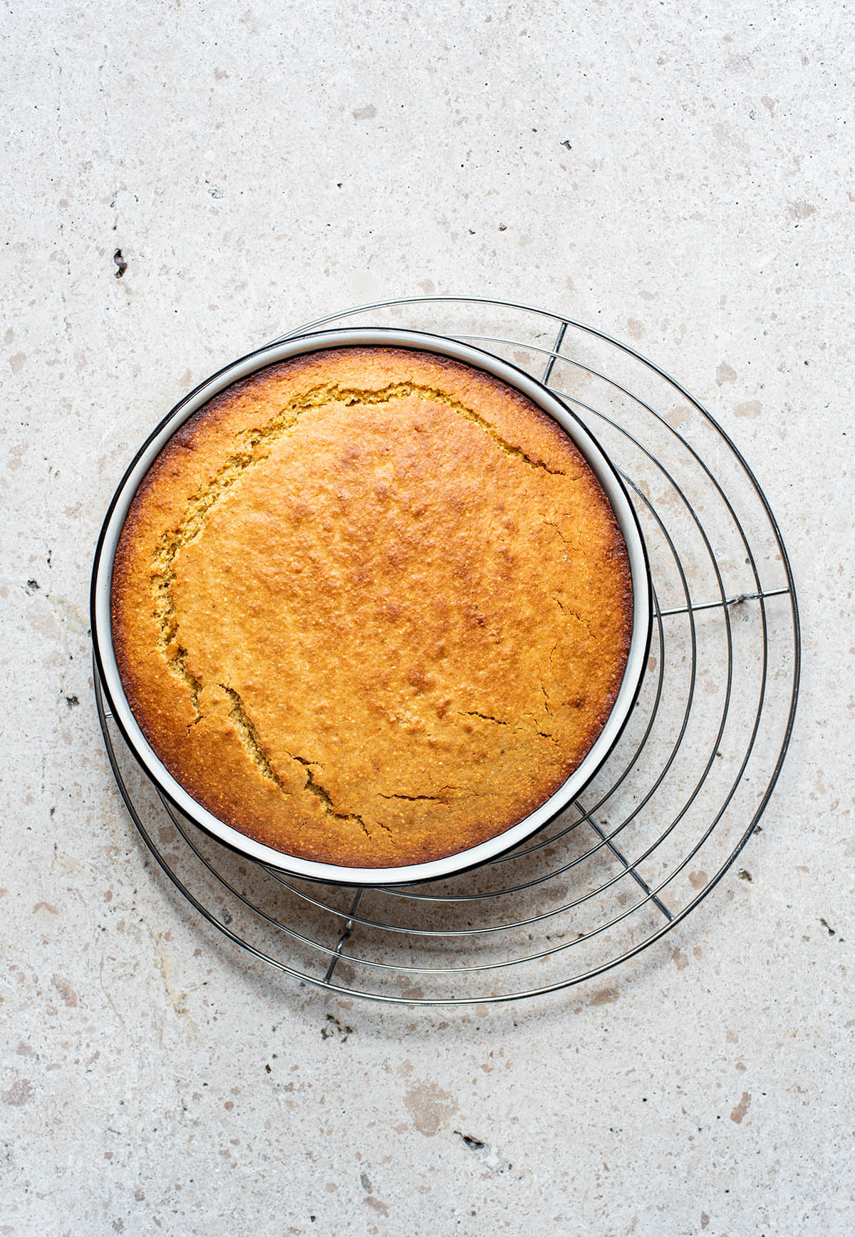 Cornbread in a round baking tin on a cooling rack.