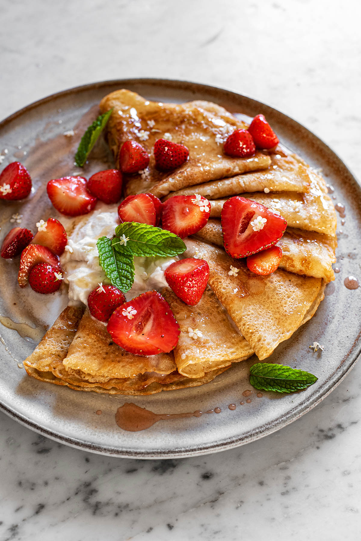 Sourdough crepes topped with fresh strawberries and cream on a ceramic plate.