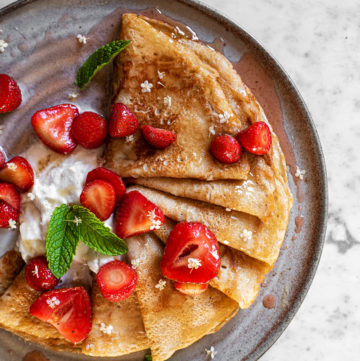 Overhead image of sourdough crepes topped with fresh strawberries and cream on a ceramic plate.