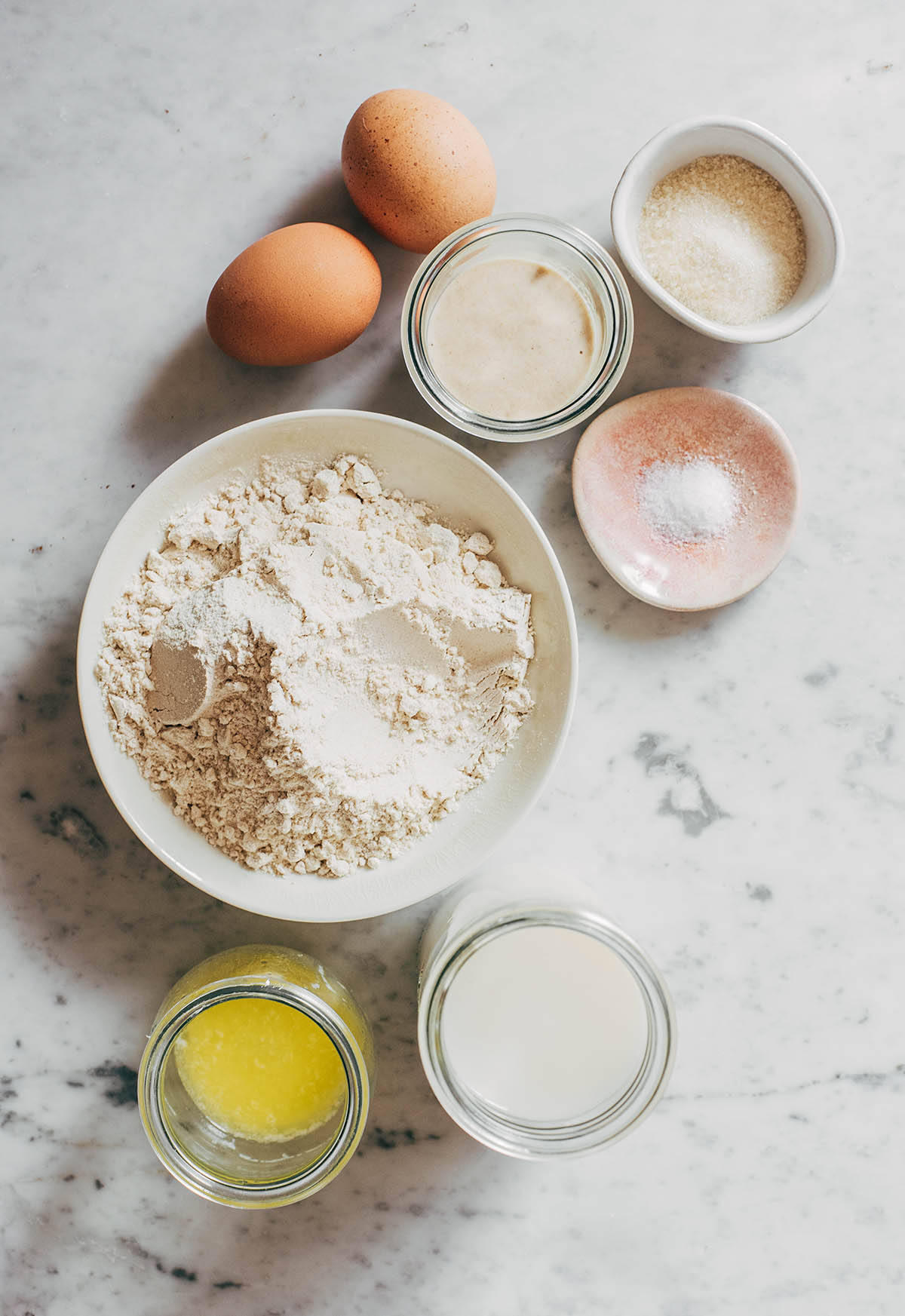 Assortment of baking ingredients in small bowls on a marble surface.