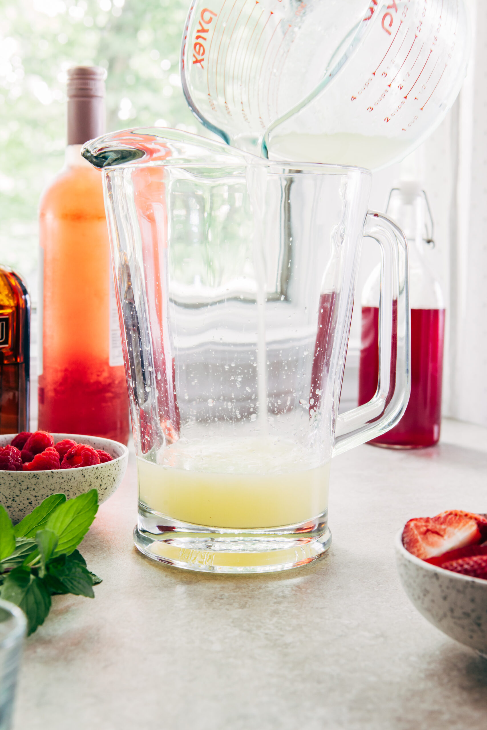 Lemon juice pouring from a measuring cup into a glass pitcher of sangria.