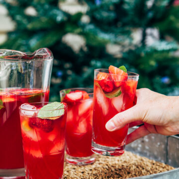 A hand taking a glass of strawberry lemonade sangria from a tray with two other filled glasses and a pitcher of sangria.