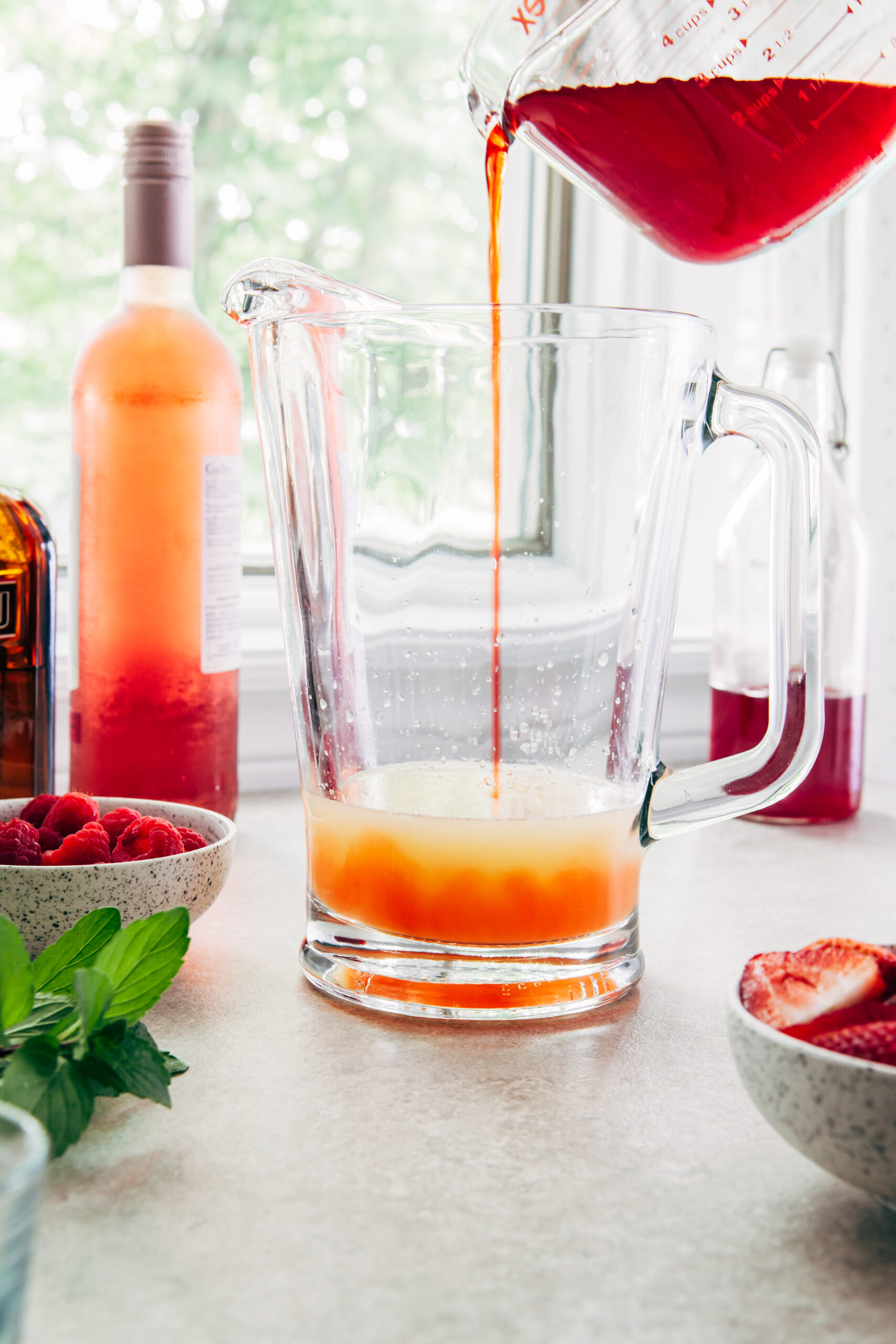 Strawberry simple syrup pouring from a measuring cup into a glass pitcher of sangria.