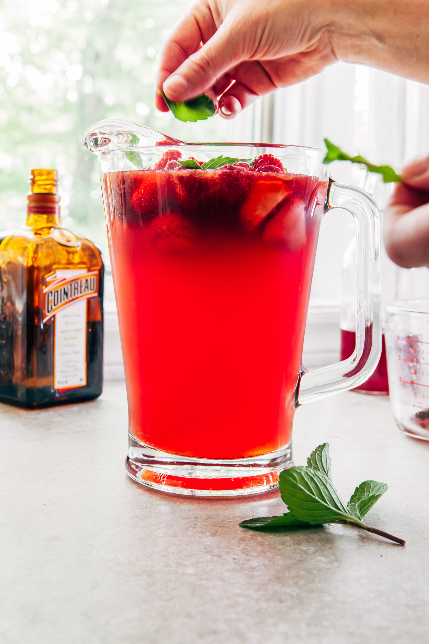 A woman's hands tearing mint leaves from the stalks to add to a pitcher of strawberry lemonade sangria.