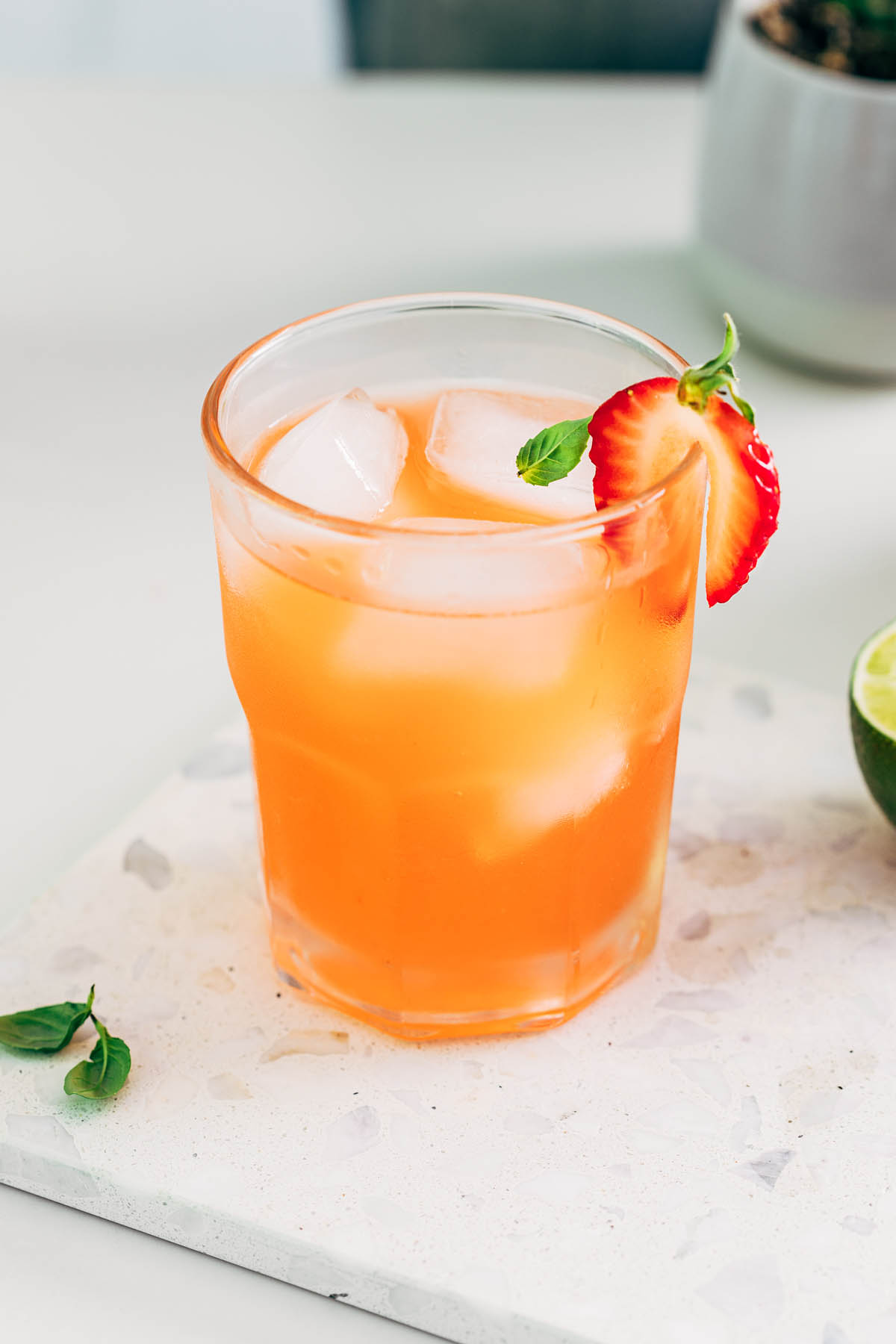 A strawberry basil margarita garnished with a strawberry.