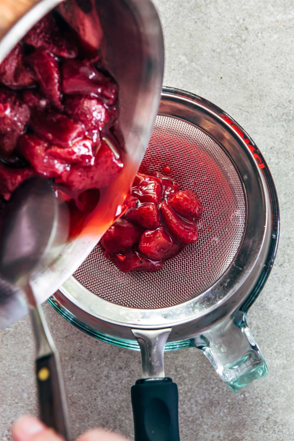 Overhead shot of a spoon scooping cooked strawberries from a pot into a Pyrex measuring cup with a sieve on top.