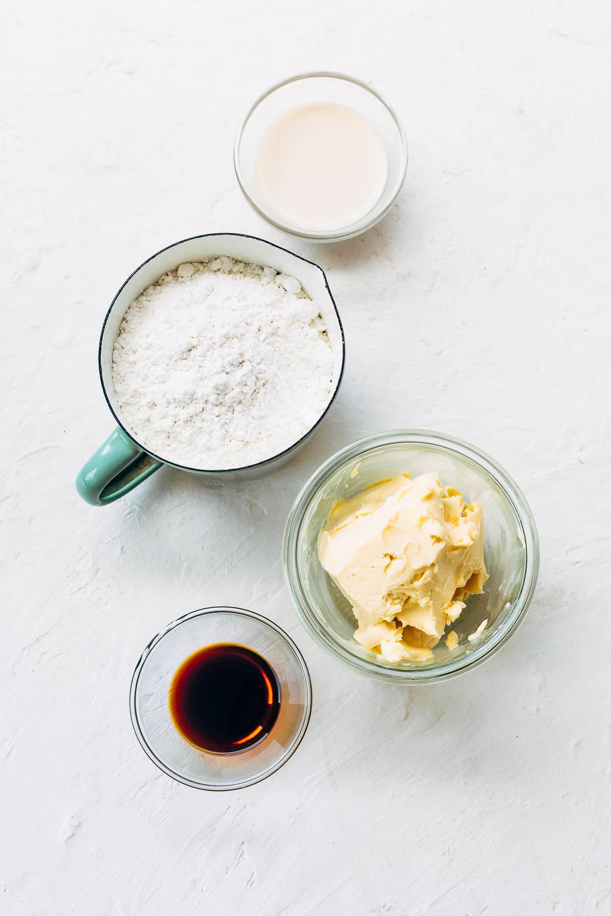Ingredients for vegan buttecream: nondairy milk, vegan butter, vanilla, and icing sugar.
