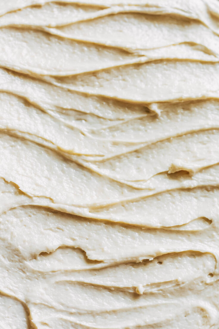 Close up of a flat surface with swoops of buttercream.
