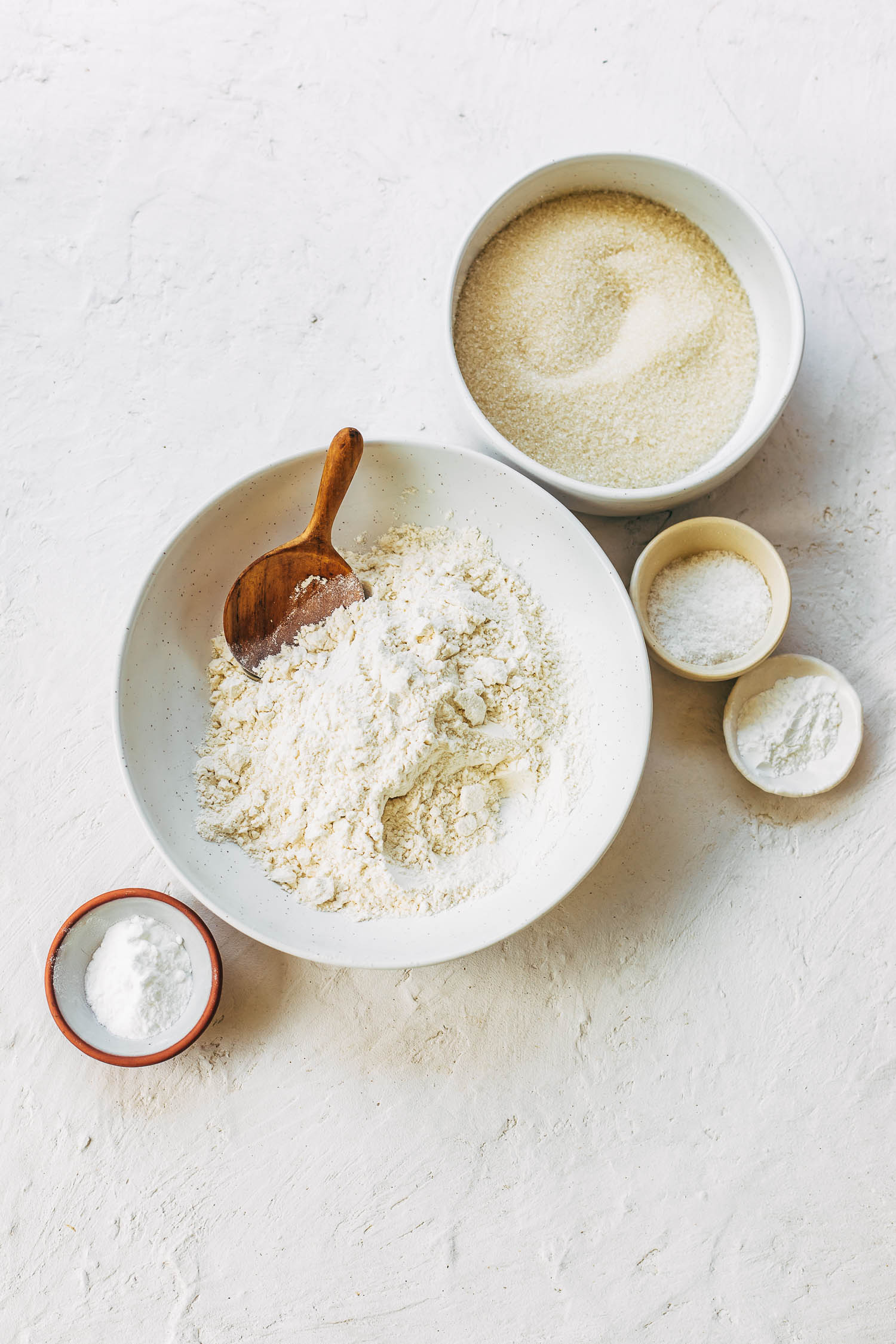 Ingredients for a vegan vanilla cake in a several bowls.