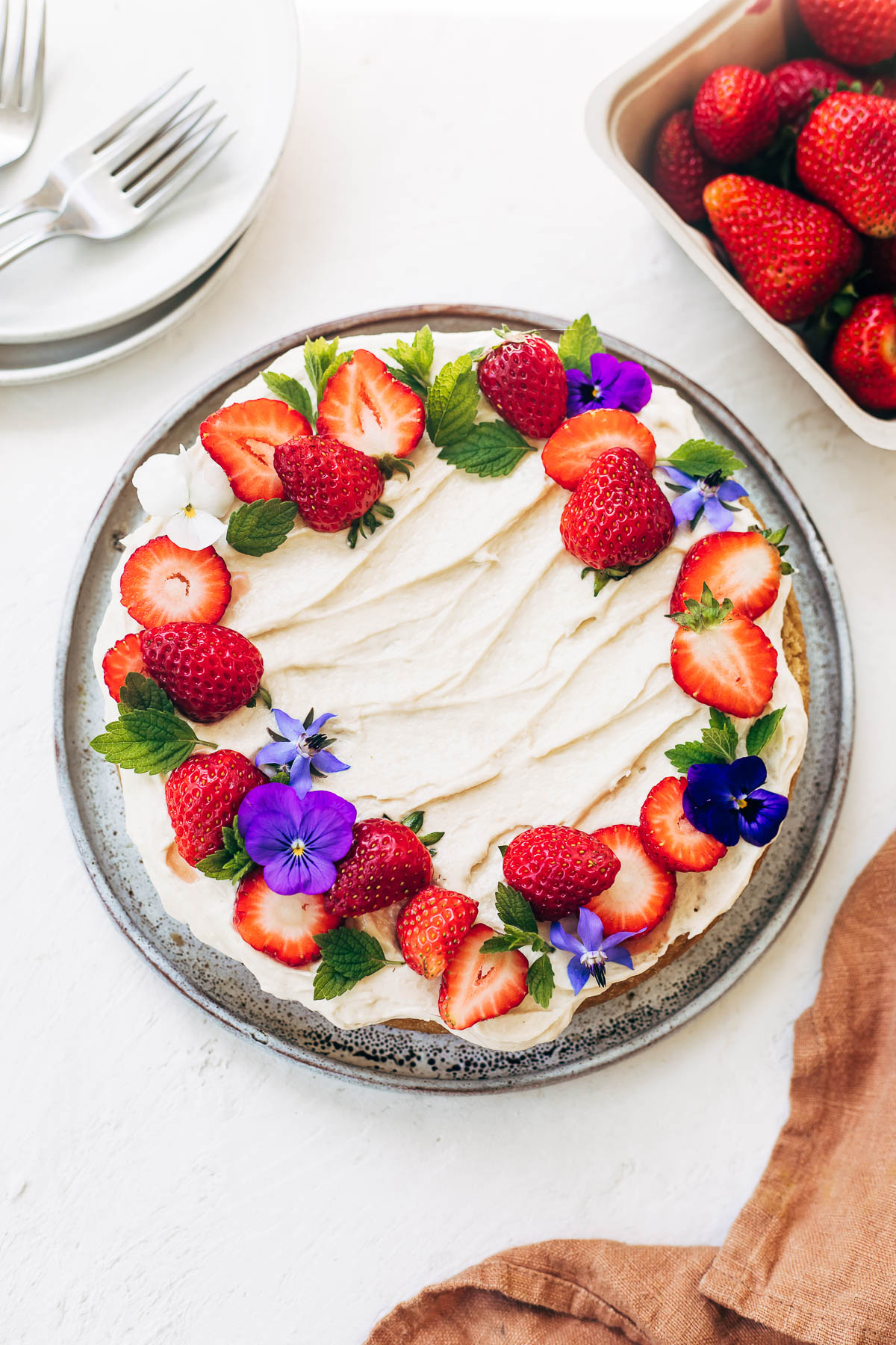 A round white cake topped with buttercream and a circle of strawberries and edible flowers.